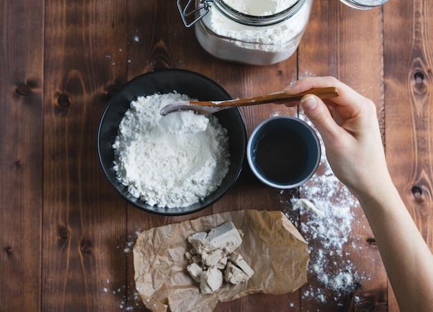 Die hand einer frau, die sauerteig mit einem holzlöffel mischt. bäckereikonzept.