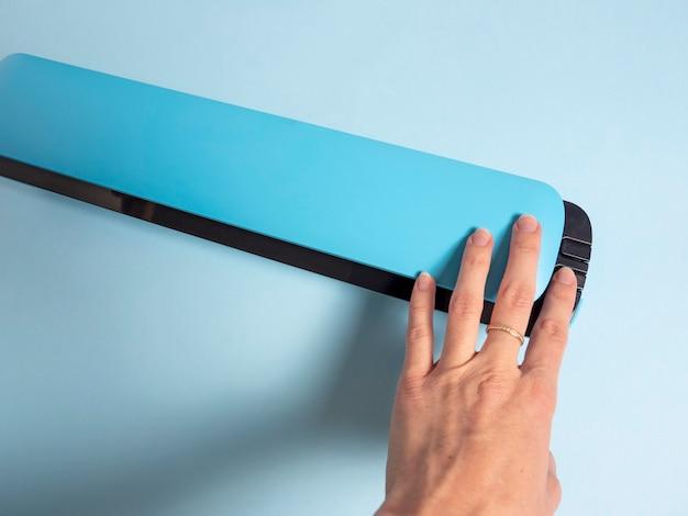 Die hand einer frau drückt den knopf eines blauen vakuumierers. das konzept der konservierung von produkten.