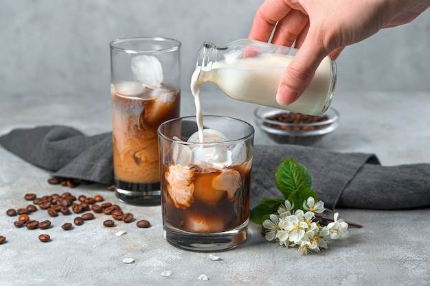 Die hand einer frau gießt milch in ein glas kaffee mit milch an einer grauen wand. zubereitung eines erfrischenden und belebenden kaffeegetränks. seitenansicht.
