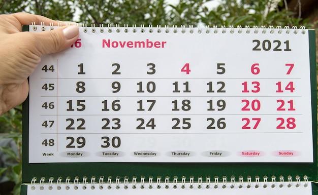 Die hand einer frau hält den kalender für november 2021, das konzept des black friday-verkaufs.