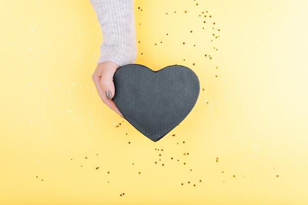 Die hand einer frau hält ein geschenk in form eines schwarzen herzens auf einem schönen gelben hintergrund mit pailletten