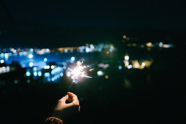Die hand einer frau hält eine brennende wunderkerze vor dem hintergrund der nachtstadt