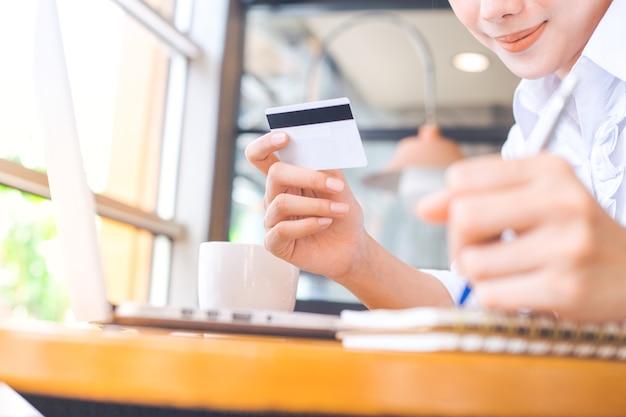 Die hand einer frau hält eine kreditkarte und benutzt einen laptop, um online zu kaufen.