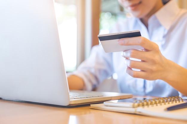 Die hand einer frau hält eine kreditkarte und benutzt einen laptop, um online zu kaufen