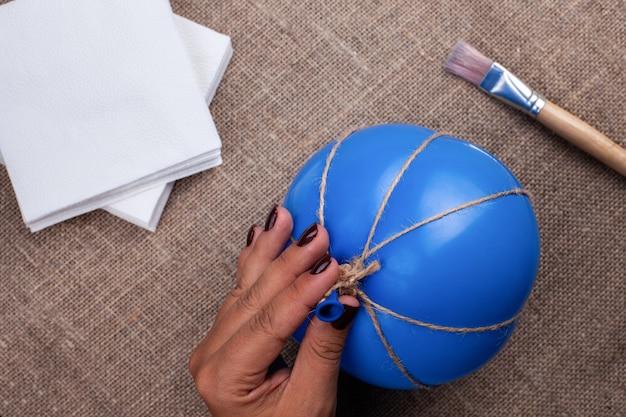Die hand einer frau hält einen ballon in juteseil gewickelt, der prozess der herstellung eines pappmaché-kürbises, halloween-dekor.