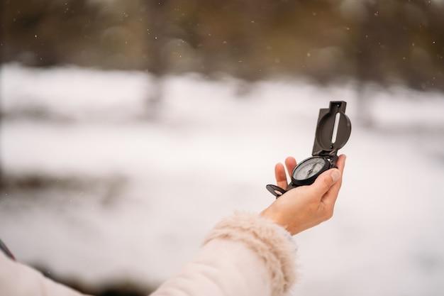 Die hand einer frau hält einen kompass in einem verschneiten wald - nahaufnahme