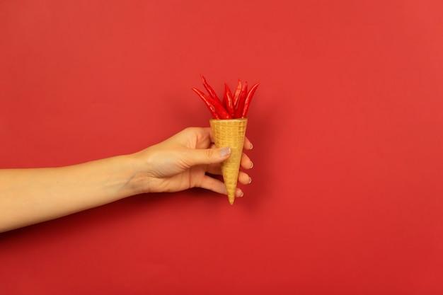 Die hand einer frau hält kleine rote paprika im waffelkegel auf einem roten hintergrund
