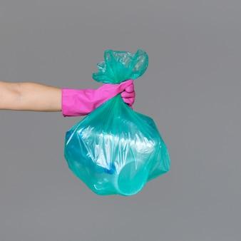 Die hand einer frau in einem gummihandschuh hält einen transparenten grünen müllsack mit leeren plastikflaschen.
