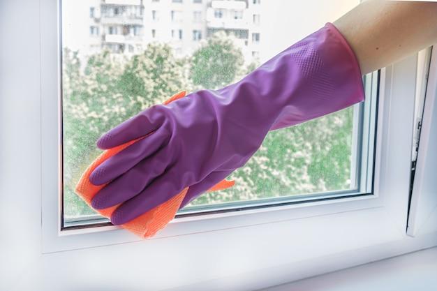 Die hand einer frau in einem lila gummihandschuh wischt ein glasfenster in einem raum mit einem lappen ab