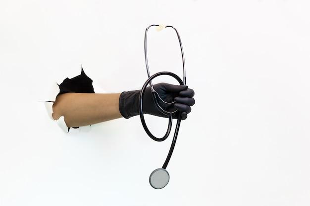 Die hand einer frau in einem schwarzen gummihandschuh hält ein stethoskop durch zerrissenes weißes papier