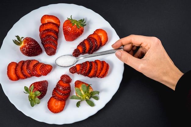 Die hand einer frau in einer draufsicht von natürlichen erdbeeren auf einem weißen teller mit einem löffel zucker auf schwarz