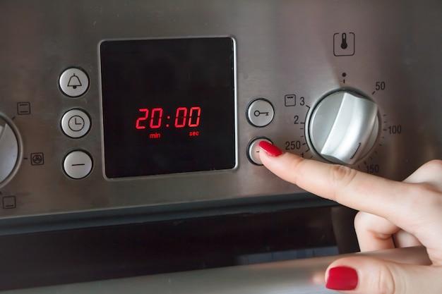Die hand einer frau legt eine zeit und eine temperatur auf den ofen