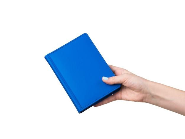 Die hand einer frau mit einem blauen notizbuch, das auf einer weißen oberfläche lokalisiert wird