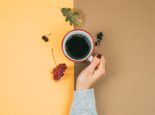 Die hand einer frau mit einer tasse kaffee und getrockneten blättern. herbstkonzept.