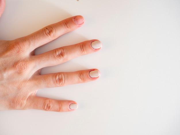 Die hand einer frau mit teilweise lackierten nägeln auf weißem hintergrund. das konzept der maniküre. kosmetologie