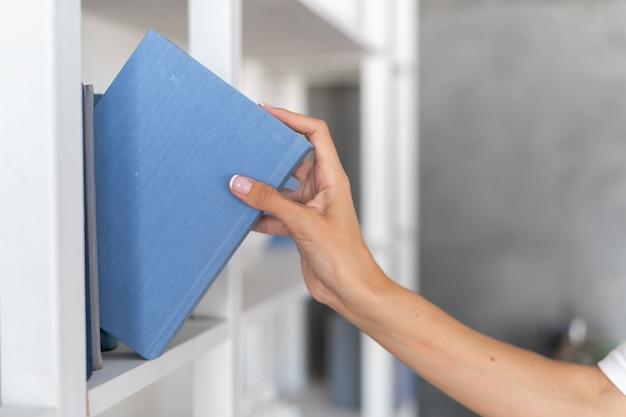 Die hand einer frau nimmt ein buch aus einem bücherregal, wählt aus, was sie an einem winterlichen herbstabend liest