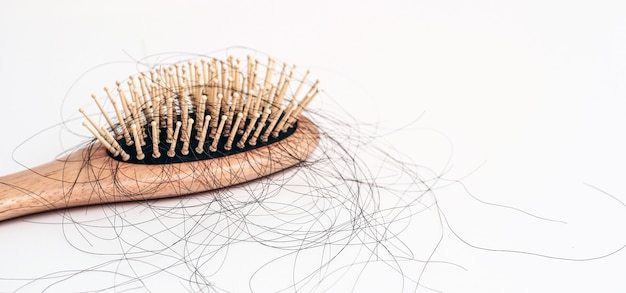 Die hand einer frau packt die fehlenden haare auf der bürste, die auf weißem hintergrund haarausfall isoliert ist