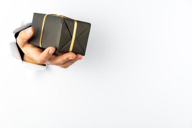 Die hand einer frau schlägt gegen eine weiße wand, eine geschenkbox in ihrer handfläche. es gibt einen urlaub hinter der mauer. speicherplatz kopieren