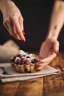 Die hand einer frau, welche die blaubeeren über dem fruchttörtchen auf holztisch hinzufügt