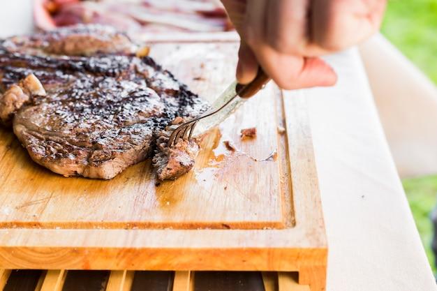 Die hand einer person, die das messer und gabel schneidet, schnitt gegrilltes rindfleischsteak auf hackendem brett