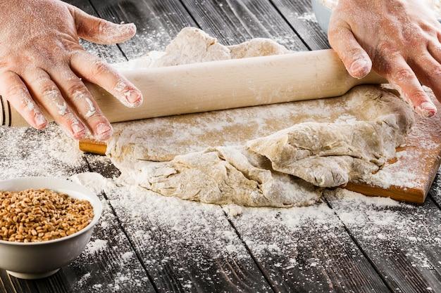 Die hand einer person, die den teig mit nudelholz auf dem küchentisch ausdehnt