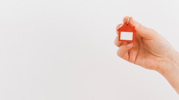 Die hand einer person, die haus keychain auf weißem hintergrund hält