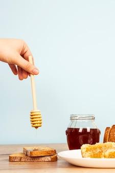 Die hand einer person, die honig auf brotscheibe auf holztisch gießt