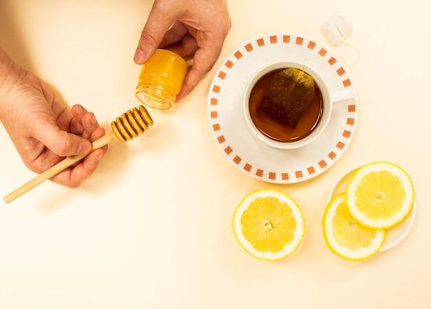 Die hand einer person, die honig vom glas für gesunden tee emporragt