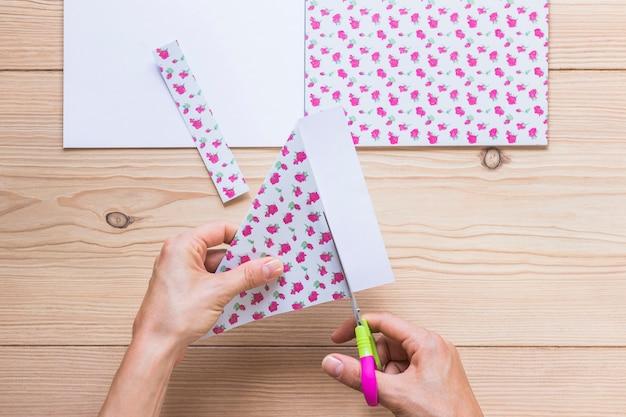 Die hand einer person, die sammelalbumpapier über der tabelle schneidet