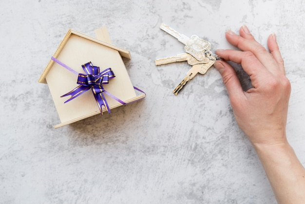 Die hand einer person, die schlüssel nahe dem holzhausmodell mit purpurrotem bogen auf konkretem hintergrund hält