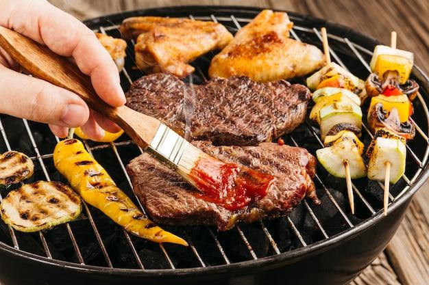 Die hand einer person, die soße auf gegrilltem steak über grill verbreitet