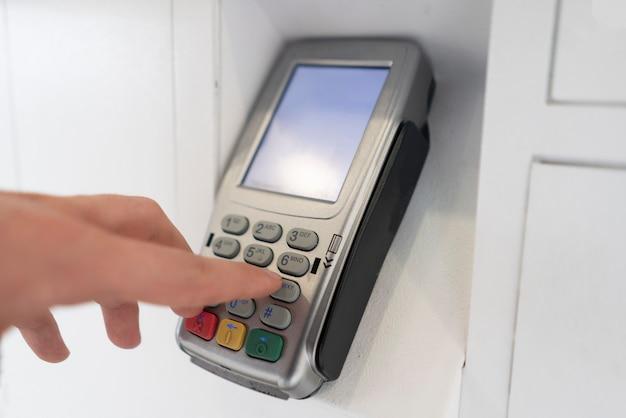 Die hand einer person gibt das passwort ein und drückt die knöpfe, um eine zahlung zu tätigen
