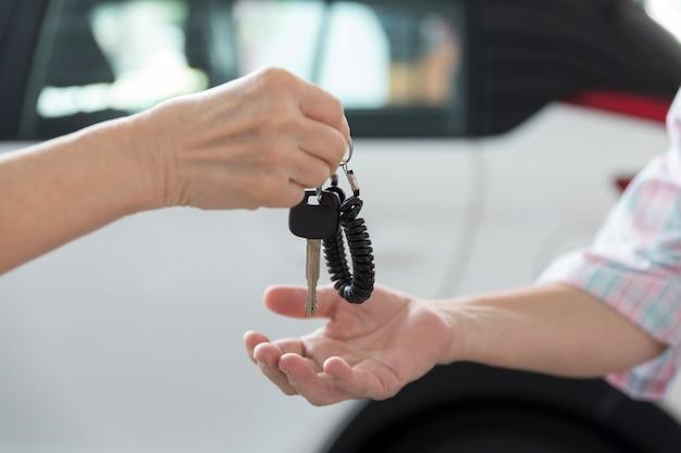 Die hand einer person gibt der anderen person den autoschlüssel