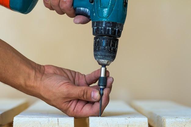 Die hand eines arbeiters schraubt mit einem akkuschrauber eine schraube in ein holzbrett. mann zimmermann bei handgemachter arbeit