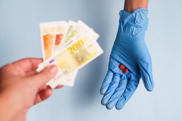 Die hand eines arztes in einem blauen medizinischen handschuh hält pillen, und die hand des patienten hält ihm euro-geld für eine gebühr für medikamente aus.