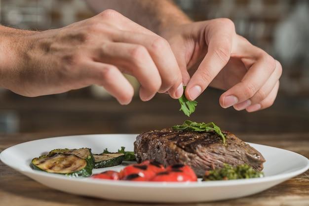 Die hand eines chefs, die koriander auf gebratenem rindfleisch verziert