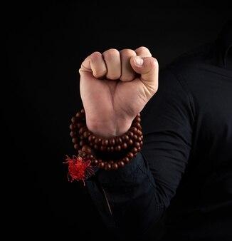 Die hand eines erwachsenen mannes zeigt mushti mudra