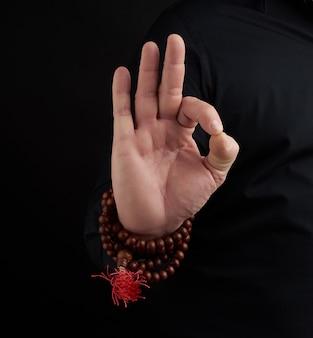 Die hand eines erwachsenen mannes zeigt om mudra
