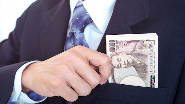 Die hand eines geschäftsmannes, der geld in einer anzugtasche fängt. anlagerichtlinien für unternehmensgewinne.