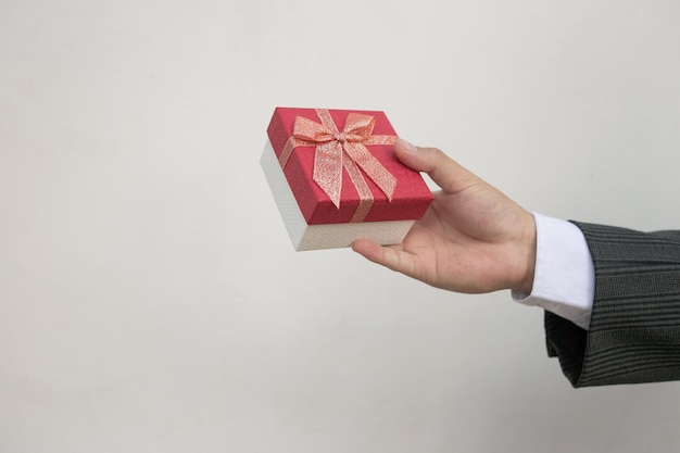 Die hand eines geschäftsmannes tauchte auf und eine kleine geschenkbox mit einem roten bogen, der auf tafel steht