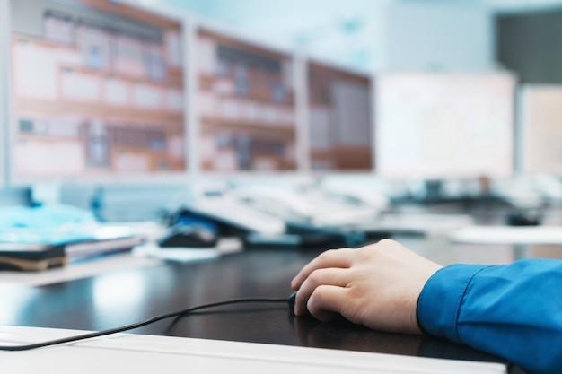 Die hand eines ingenieurs hält eine pc-maus und steuert die arbeit zur erzeugung elektrischer energie.