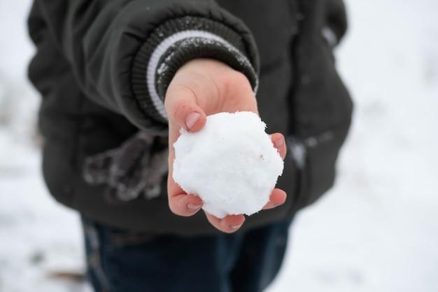 Die hand eines kindes, die einen runden schneeball hält.