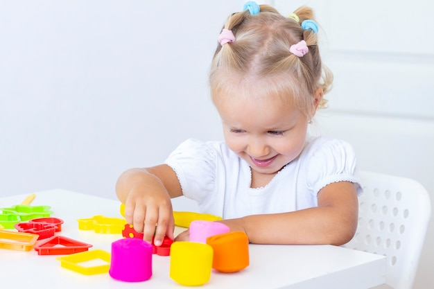 Die hand eines kleinen kindes drückt farbige plastilinstücke zusammen