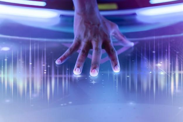 Die hand eines künstlers mit schallwellentechnologie berührt die bühne mit remixten medien