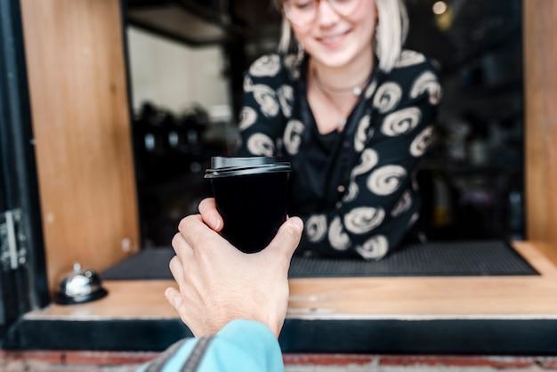 Die hand eines kunden holt in einem kleinen café einen kaffee zum mitnehmen ab.