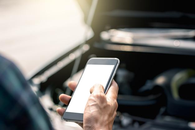 Die hand eines mannes benutzt ein smartphone auf einer verkehrsstraße, während ein auto zusammenstößt.