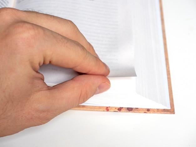 Die hand eines mannes blättert in nahaufnahme durch eine leere seite eines buches. selektiver fokus