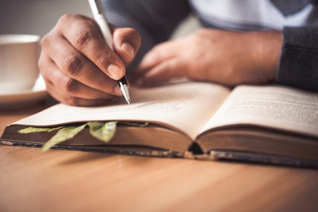 Die hand eines mannes, der einen stift hält und kenntnisse in einem notizbuch nimmt.
