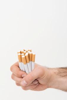 Die hand eines mannes, die haufen von zigaretten lokalisiert auf weißem hintergrund hält