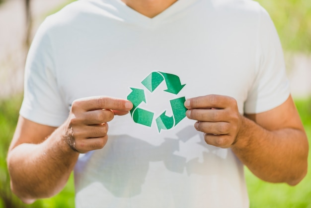 Die hand eines mannes, die recycling-symbol hält